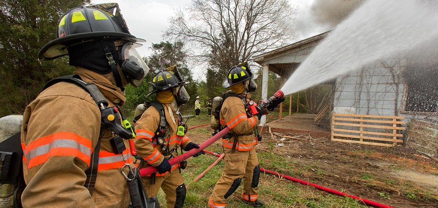 Firefighters with water hose