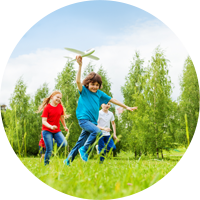 kids running field airplane trees