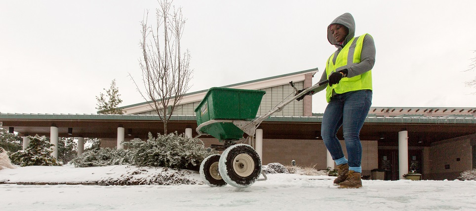 A worker spreading salt on a sidewalk during a snow event