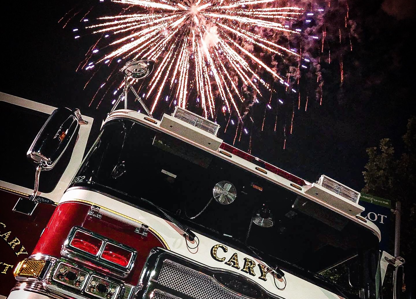 Firetruck with fireworks exploding overhead