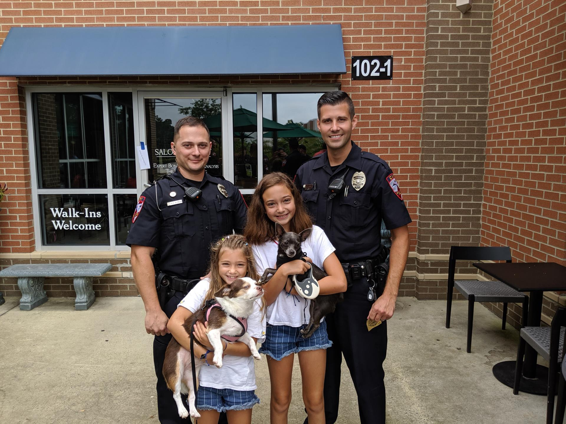 Police officers with two children holding puppies